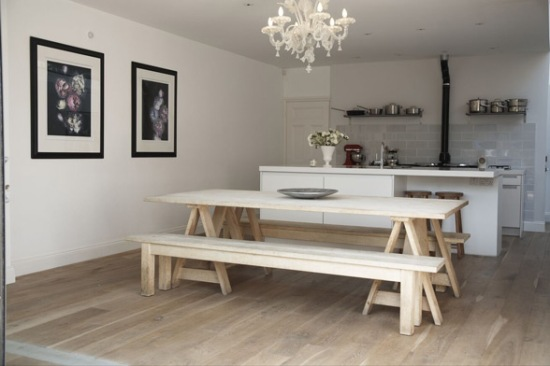white kitchen with wooden bench and chandelier